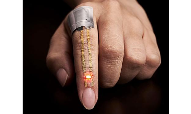 皮膚貼り付け型ナノメッシュ電極を人差し指に装着し、フレキシブルバッテリーから電力を供給して発光ダイオードを点灯させた