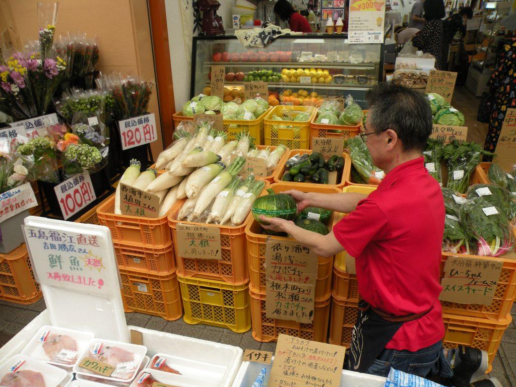 生産者市場さんむーんの社長さんが店先で販売しています。