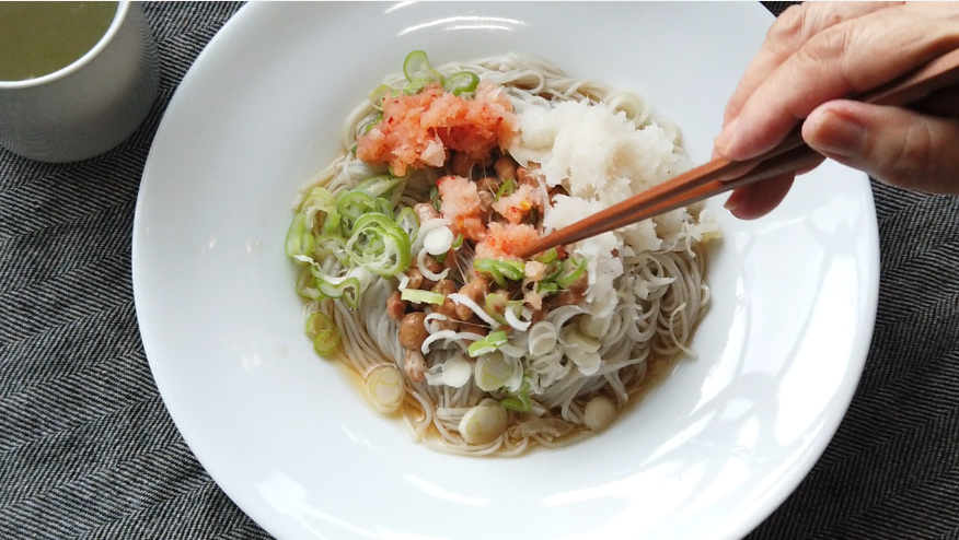 【納豆おろし素麺レシピ】4.器に黒ごまそうめんを盛りつけ、納豆、長ネギ、大根おろし、もみじおろしをのせて、麺つゆをかけて出来上がり!