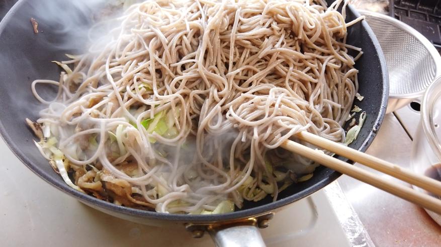 【ソース焼きそばの作り方】8.7に合わせ調味料の半量、蒸し麺を加えて、ほぐし炒めます。