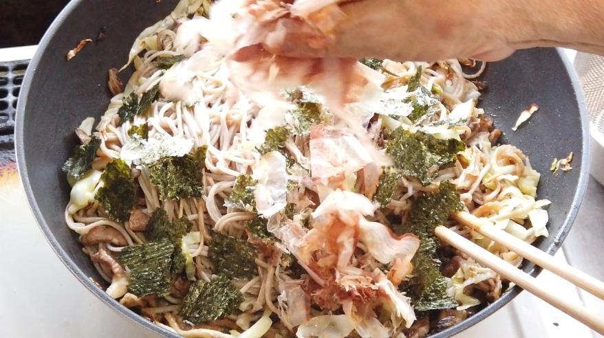 【ソース焼きそばの作り方】9.火を止めて、かつお節、焼き海苔を手でちぎって加えて、混ぜます。