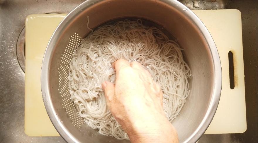 【油そば風そうめんレシピ】4.黒ごまそうめんはたっぷりのお湯で約1分茹で、ザルにあげ、水で洗う。