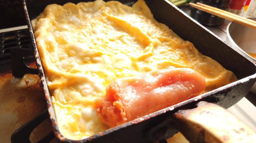 【明太卵焼きレシピ】2.卵焼き器に油を敷いて、卵を入れ、明太子をのせ、卵を巻きます。
