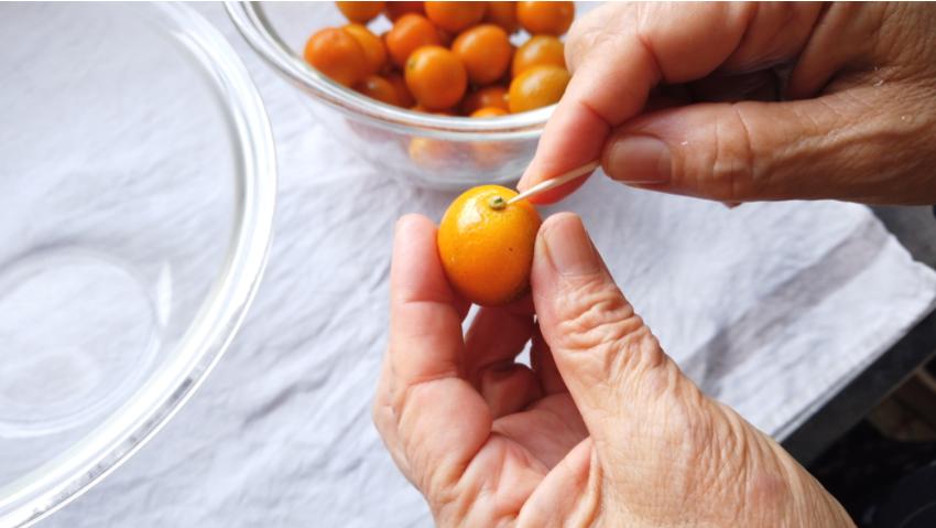 【金柑のはちみつ漬けの作り方】1.金柑のへたを取り除く。