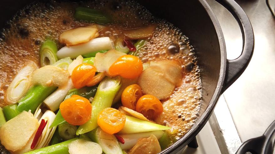 【鶏もも肉と金柑のはちみつ漬けの煮物レシピ】3.長ねぎ、生姜、鷹の爪、ごま油、醤油、日本酒、砂糖、金柑のはちみつ漬けのシロップを入れて、強火にかけ沸騰させ、沸騰したら、中火で10分ほど煮る。