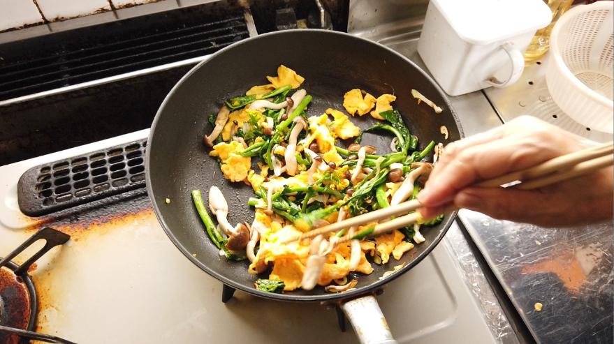 【菜の花と炒り卵の炒め物レシピ】3.フライパンに油を敷いて、長ネギを入れて、香りをつけたら、菜の花の茎の部分から炒め、菜の花の花の部分、ブナシメジを加えて、火が通ったら、炒り卵を加えます。