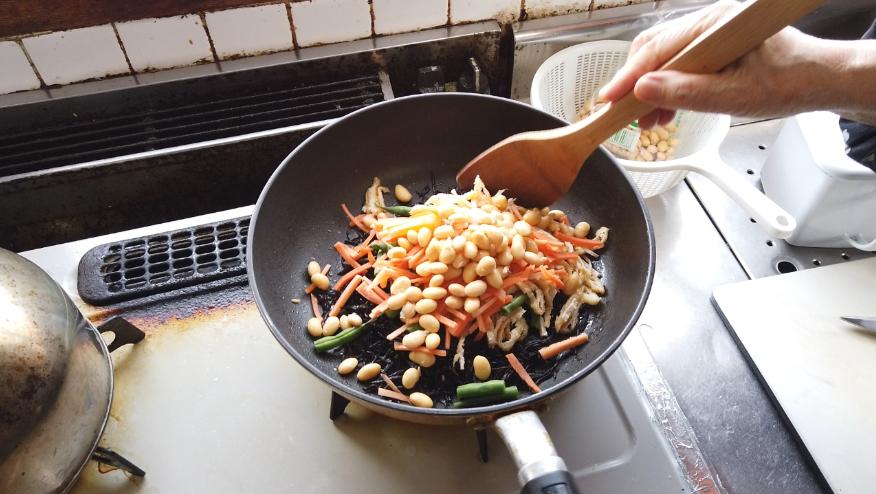 【ひじきの煮物レシピ】2.フライパンに油を敷いて、ひじきを軽く炒めたら、人参、油揚げ、ゆで大豆を加えて、全体に油を回すように炒めます。