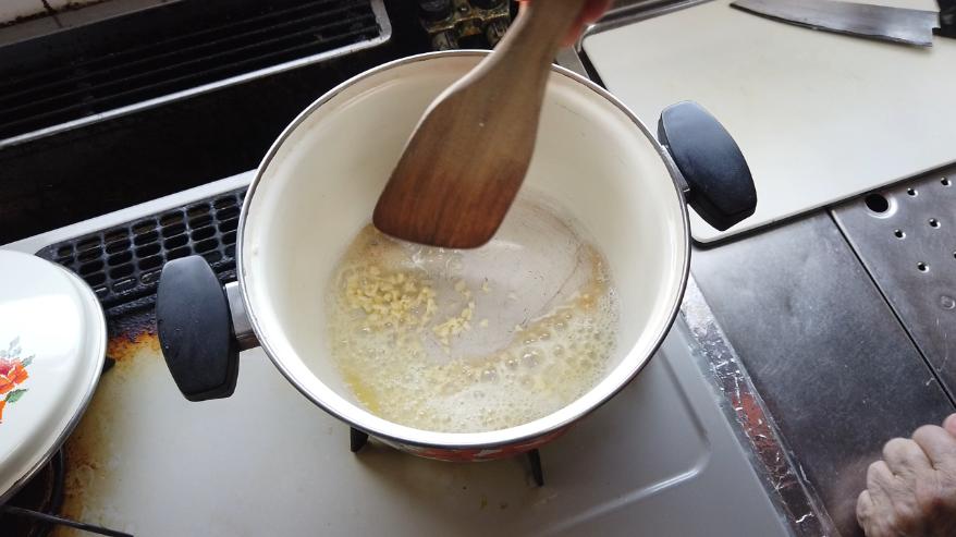 【オニオンスープレシピ】2.ほうろう鍋にバターを入れて熱し、にんにくを入れて香りを出します。