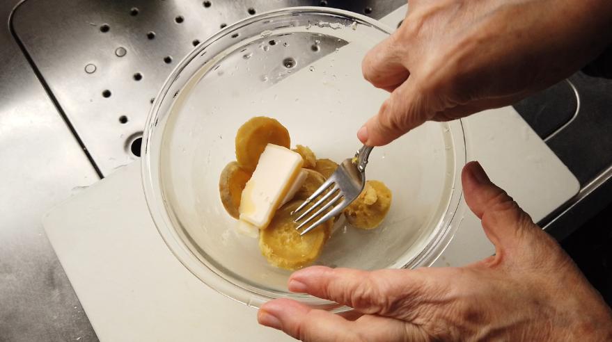 【レーズンを使ったさつまいものスイートサラダレシピ】2.サツマイモの皮をむき、ボウルに入れて、バターを加えフォークでつぶします。