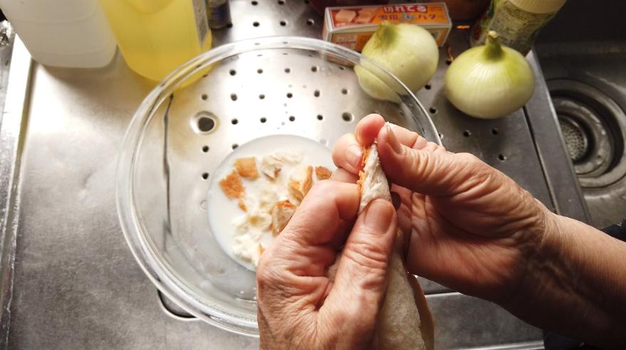 【煮込みハンバーグレシピ】1.ボウルに牛乳を入れ、食パンをちぎって浸しておきます。