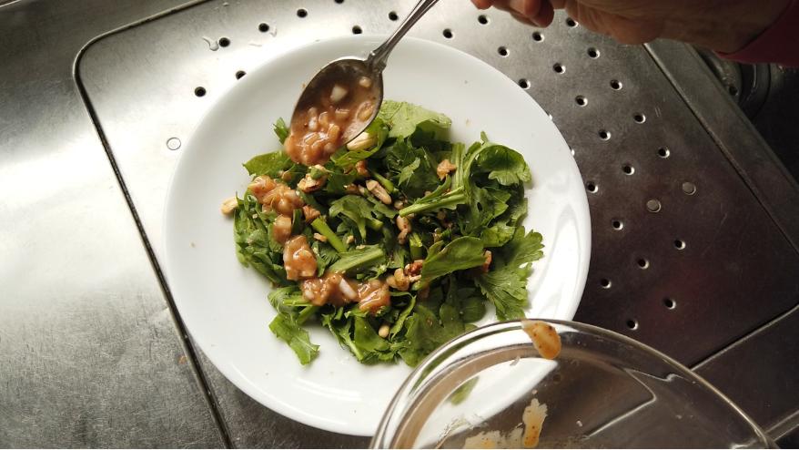 【春菊サラダレシピ】3.器に春菊とカシューナッツ・クルミを入れて合わせ、万能玉ねぎ味噌ドレッシングをかけて出来上がり!