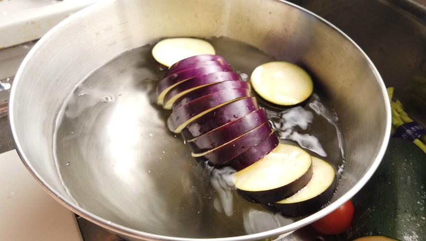 【夏野菜の揚げびたしレシピ】1.なすのヘタを落とし、輪切りにして水にさらします。ズッキーニを輪切りにします。パプリカを半分に切り、種をとって縦4等分にします。かぼちゃは種とわたを取り約5mm厚さにスライスします。ししとうを半分に切りタネを出します。オクラを斜めに切ります。アスパラガスを3等分に切ります。野菜は水気をよく拭いておきます。
