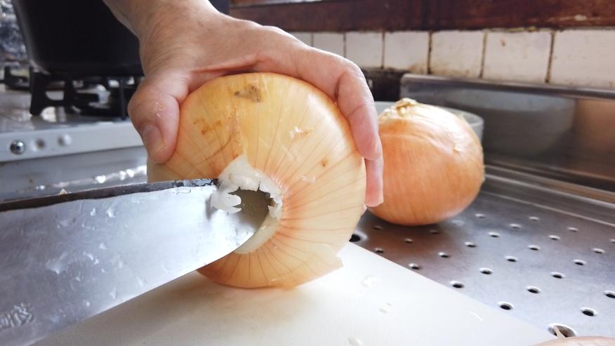 【玉ねぎのポタージュレシピ】1.玉ねぎ容器づくり。玉ねぎの底の中心に包丁の先を斜めに刺して、玉ねぎを回し、芯に穴を開けます。玉ねぎを上1/3~1/4をカットします。底の穴から指で押して中を外します。小さな皮を使って、玉ねぎ容器の底を作ります。
