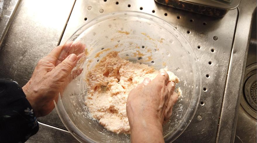 【豆腐ハンバーグ(ひじきの煮物入り)レシピ】2.ボウルにひき肉、だしの素、こしょうを入れて練り、豆腐を加えてよく混ぜます。
