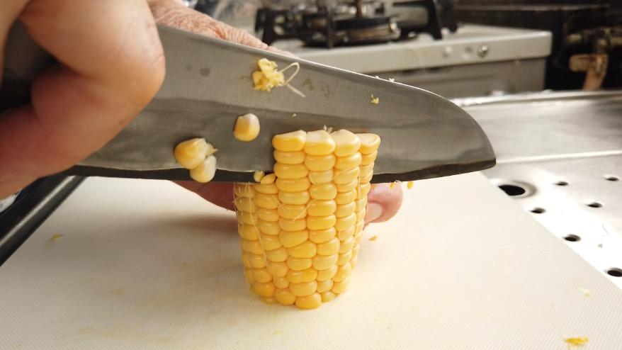 【コーンポタージュレシピ】1.トウモロコシを包丁で1/3にカットし、実をそぎます。