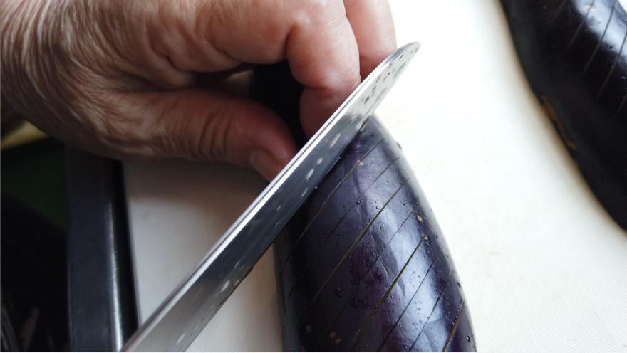【フライパンで焼き茄子レシピ】1.ナスのへたを取り、なすを縦半分に切り、なすの背の部分に5ミリ間隔で切れ目を入れます。