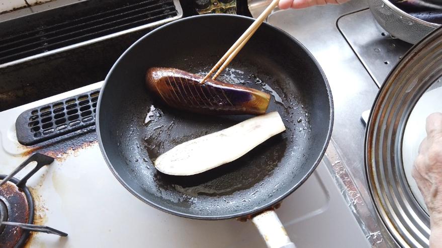 【フライパンで焼き茄子レシピ】2.フライパンに油を敷き、なすの背の部分を底にして、フタをして焼きます。3分ほど焼いて途中で焼き加減を確認して、焼けてきたら、ひっくり返して焼きます。