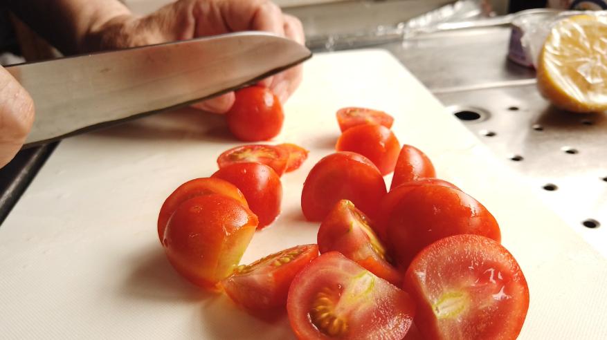 【ミニトマトとツナの梅シロップマリネレシピ】1.ミニトマトのへたを切り、半分に切ります。