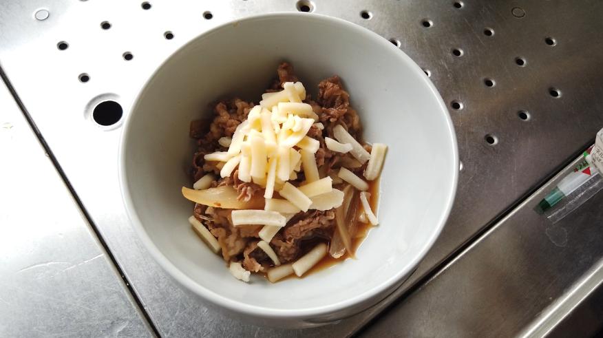 【牛丼レシピ】5.チーズ牛丼は、耐熱容器に(5)を加え、上からピザ用チーズをかけて、電子レンジ(500W)でチーズが溶けたら、ご飯をついだ丼にかけて出来上がり!