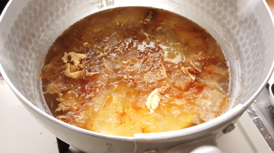 【肉汁つけ蕎麦レシピ】1.鍋に水と昆布(表面を固く絞ったふきんで軽くふきましょう)、いりこ(煮干し)、干し椎茸を入れて15分置き、弱火にかけます。だしが出たら(色が黄金色に変わったら)、火を止め、昆布・いりこ・干し椎茸を取り出します。かつお節を加えて、1~2分経ったら(かつお節が鍋底に沈む)、ボウルとざるを重ねたうえにキッチンペーパーを敷いて、こします。
