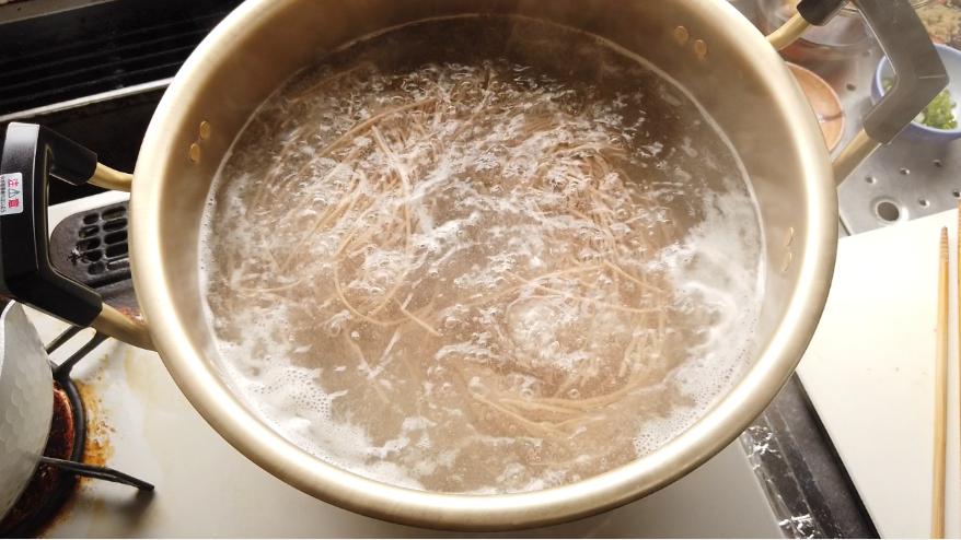【肉汁つけ蕎麦レシピ】4.えごま蕎麦をたっぷりのお湯で4分ゆで、ざるにあげ、水で洗います。