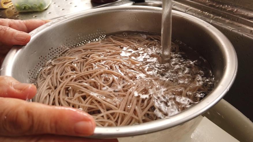 【月見とろろ蕎麦の作り方】2.えごま蕎麦をたっぷりのお湯で4分ほどゆで、ザルにあげ、水で洗います。