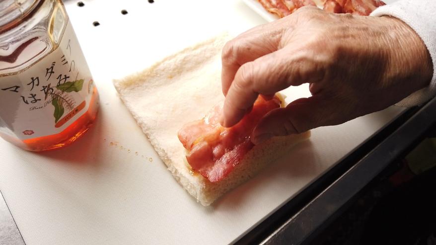 【チーズベーコンハチミツロールレシピ】3.食パンの端の部分に蜂蜜を塗り、その上に丸めたスライスチーズ、ベーコンをのせて、くるくると丸め、端に溶き卵を塗り、しっかりとくっつけます。