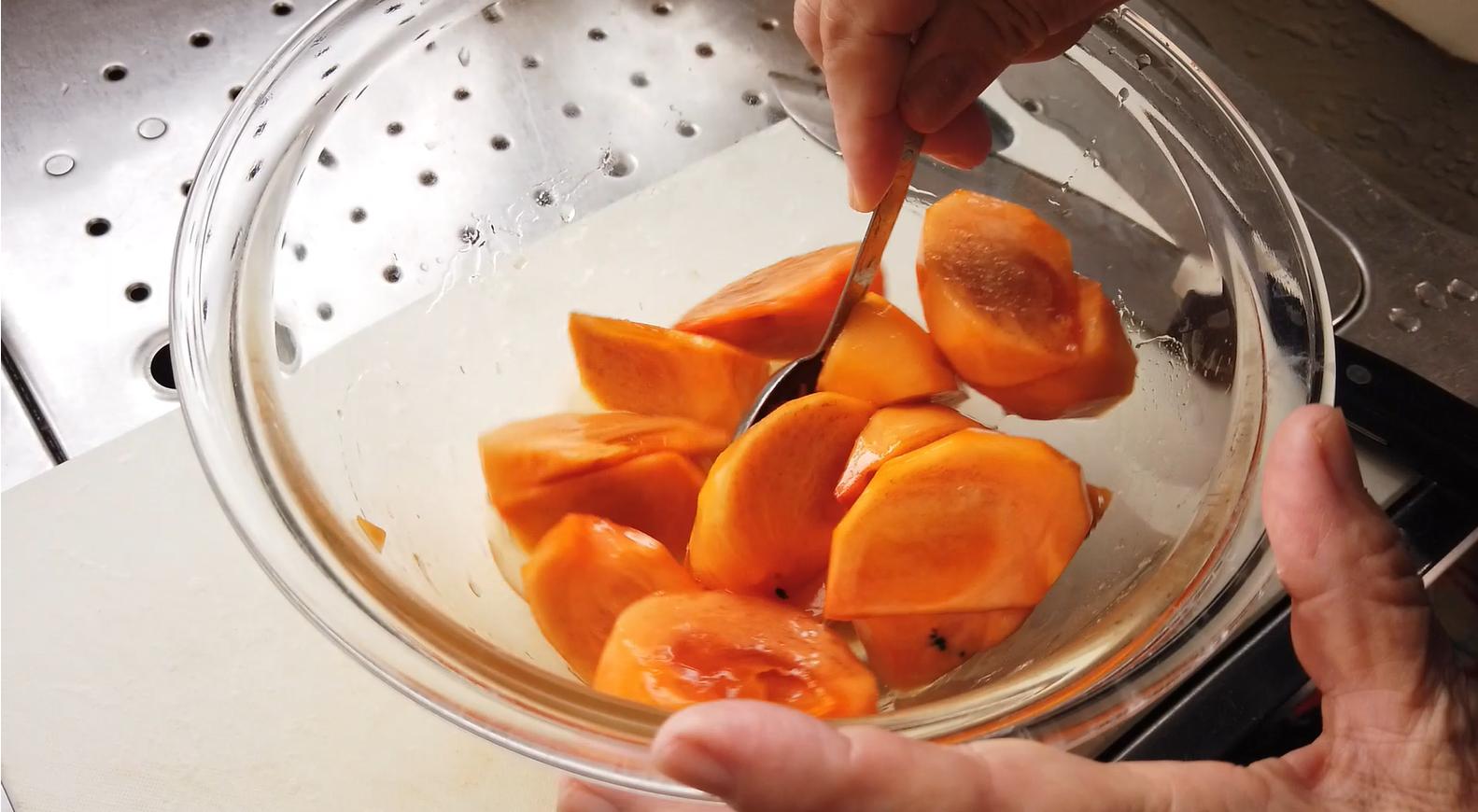 【柿とリンゴのマリネレシピ】3.ボウルにくし切りした柿、レモン汁、ハチミツを加えて和えたら、1時間ほど置きます。