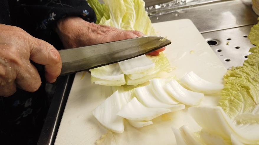 【白菜と手羽先のスープレシピ】1.下ごしらえ。白菜をはがして汚れを洗い流したら、大きい葉は縦半分に切り、食べやすい大きさに切ります。チンゲン菜も同様に葉の部分を切り離したら汚れを洗い流し、大きい葉を縦半分に切ります。生姜は皮ごと薄切りにします。