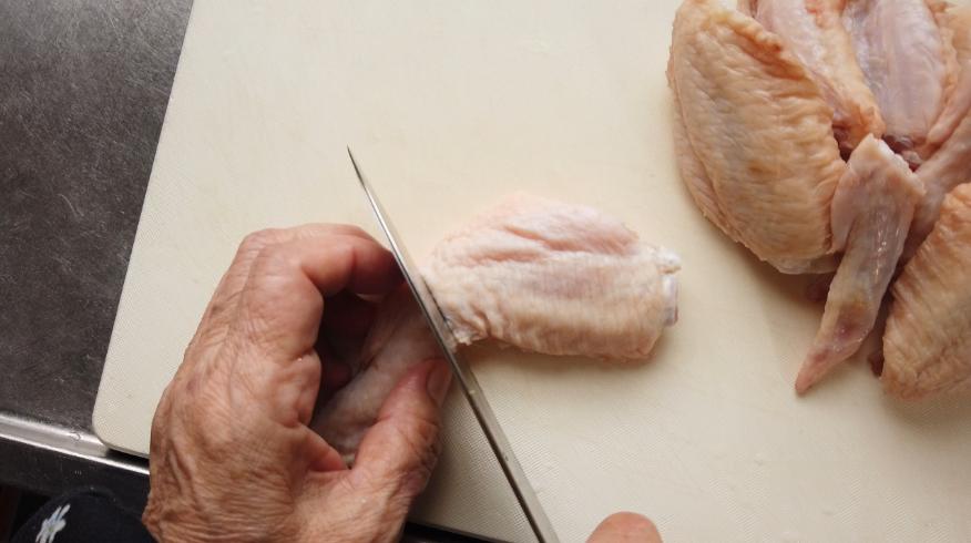 【白菜と手羽先のスープレシピ】2.鶏の手羽先を関節の部分に包丁を当てて2つに切り分けます。