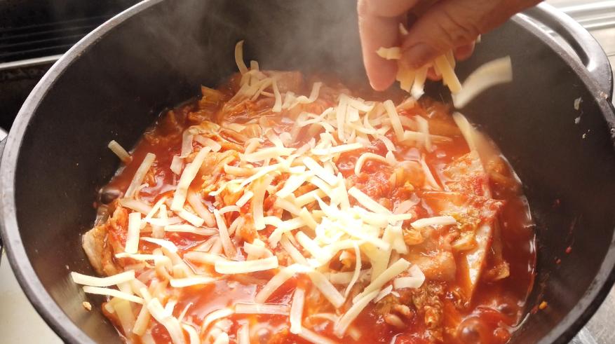 【白菜と豚バラのトマトミルフィーユ鍋レシピ】6.クッキング用とろけるチーズをかけて、蓋をして中火にかけて溶かします。