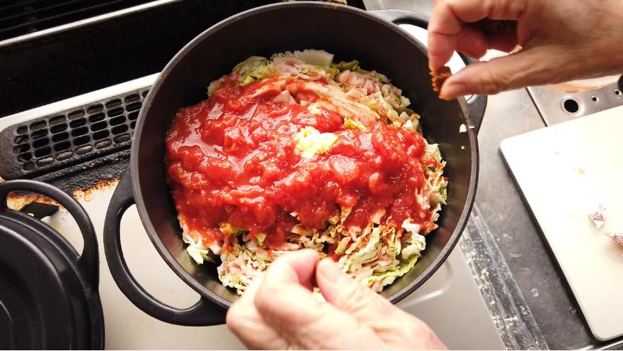 【白菜と豚バラのトマトミルフィーユ鍋】4.トマトホール缶の中身をボウルに出して手でつぶしたら、鍋に入れ、酒、おろしにんにく、固形コンソメを入れて、中火で10~15分煮ます。