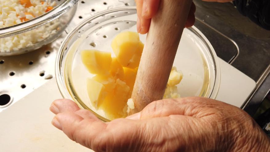 【卵コロッケレシピ1-2】1.下ごしらえ。ジャガイモは皮をむいて、芽をとり3センチ幅ほどに切り、水にさらしてから、しっかりと水を切った後に耐熱容器に入れ、ふんわりラップをして電子レンジ(500W)で5分加熱し、軽くつぶしておきます。
