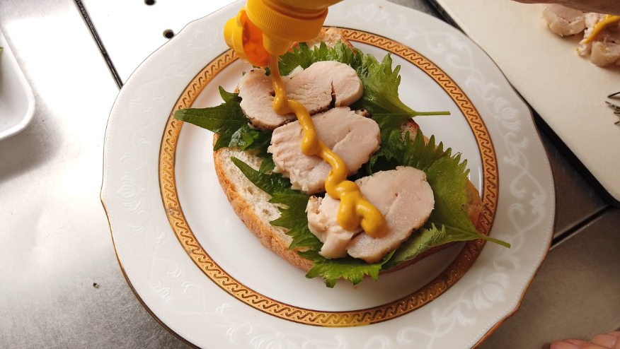 【鶏ハムの作り方4-2】4.鶏ハムをスライスし、出来るだけ薄くスライスしたライ麦パンに、鶏ハムと大葉、マスタードを塗ります。