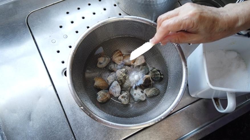 アサリと水、塩を入れて、暗いところに1~2時間ほど置いて砂抜きをします。