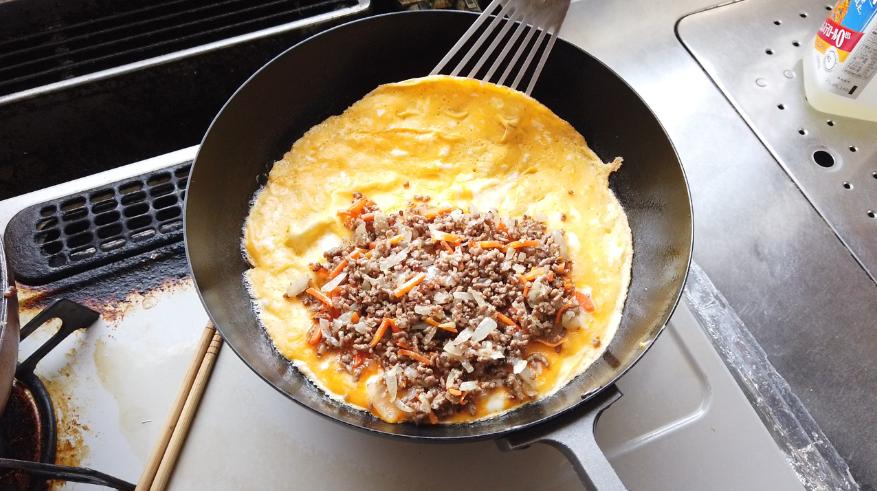 【オムレツレシピ7】7.ほとんど卵に火が通ったら、火を止め、卵の片側に(5)をのせて、卵で包みます。