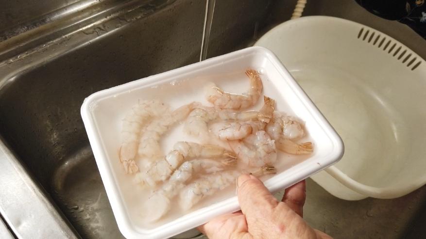 【海老とブロッコリーの炒め物レシピ1-3】1.下ごしらえ。えびの殻をむき、爪楊枝や金串などで背ワタを取り、尻尾を半分ほどカットして包丁の先でこするようにして尻尾の汚れを出し、切れ目を何か所か入れ、水洗いをして、キッチンペーパーで水気をふき取ります。