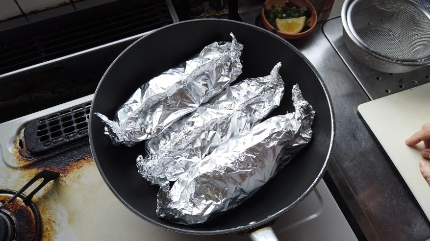 【鮭ときのこのホイル焼きレシピ4】4.フライパンに包んだものを入れて、フタをして弱火で15分ほど加熱します。